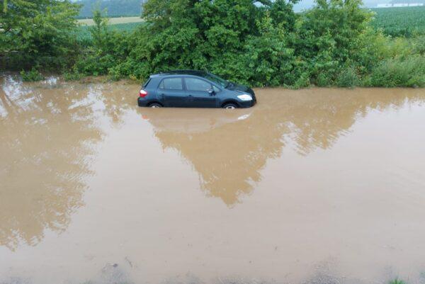 Ein Auto schwimmt wegen Starkregen weg