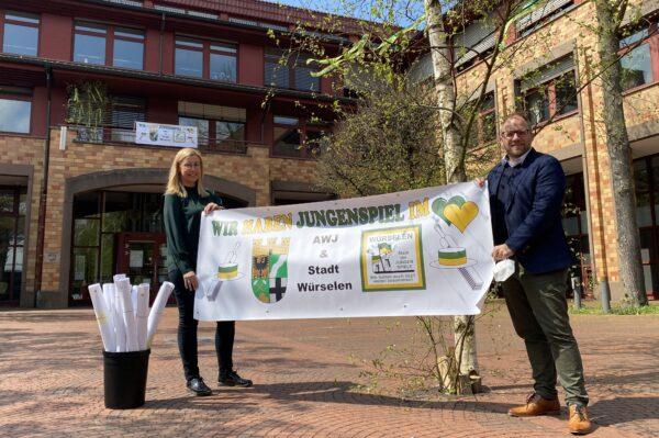 """Kathrin Hensen und Bürgermeiter Roger Nießen zeigen das Banner """"Wir haben Jungenspiel im Herzen"""""""