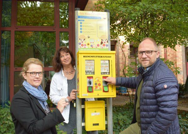 Bürgermeister Roger Nießen zieht eine Blühkapsel am Bienenfutterautomat am Rathaus auf dem Morlaixplatz