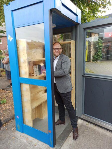Der Bürgermeister nimmt ein Buch aus dem Bücherschrank