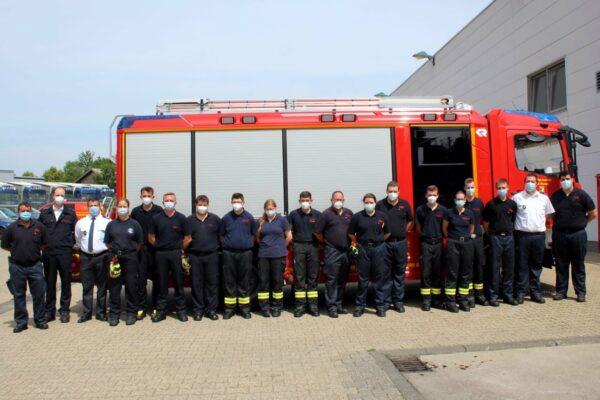 Feuerwehrleute vor einem Feuerwehrfahrzeug
