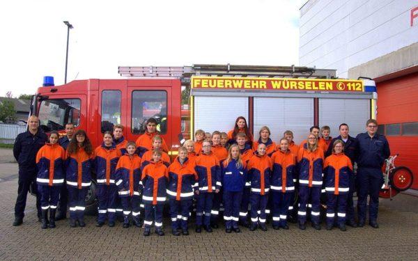 Gruppenfoto der Jugendfeuerwehr Mitte vor einem Feuerwehrauto.
