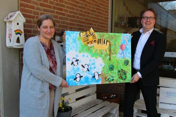 Zwei Personen halten ein Kunstwerk fest