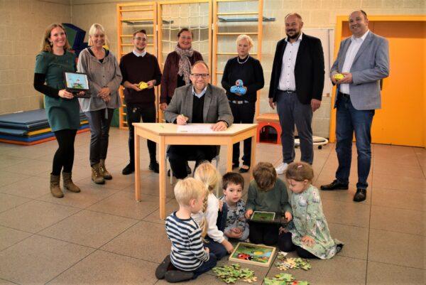 einige Menschen stehen hinter dem Bürgermeister, der ein Zertifikat unterschreibt, davor sitzen Kinder und spielen