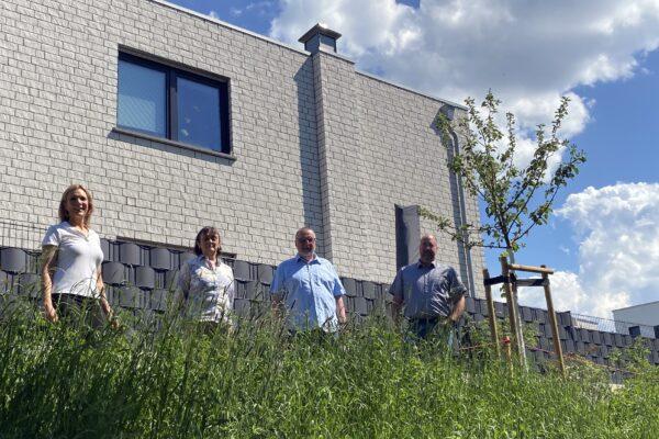 Vier Personen und ein neu gepflanzter Obstbaum sind am Wohngebiet Kapellenfeldchen zu sehen.