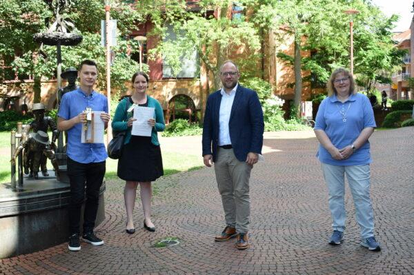 Bürgermeister Roger Nießen gratuliert zwei Auszubildenden zur bestandenen Abschlussprüfung