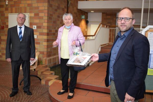 Dieter Juschka, Hanny Wendel und Roger Nießen im Foyer des Rathauses, der Bürgermeister überreicht ein Geschenk.