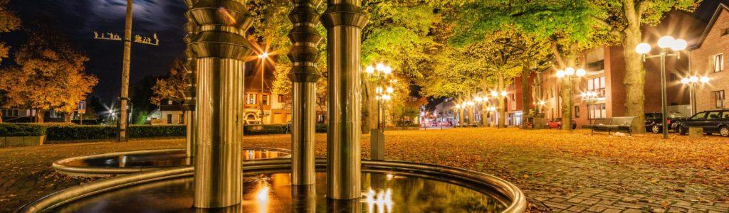 Brunnen am Lindenplatz bei Nacht. Hellerleuchtet durch die Straßenlaternen. Im Hintergrund der Maibaum der Bissener Maigesellschaft.