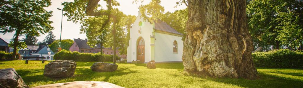 Eine Kappelle im Sonnenlicht, Ein großer Baum und Steine im Vordergrund; Würselen Pley