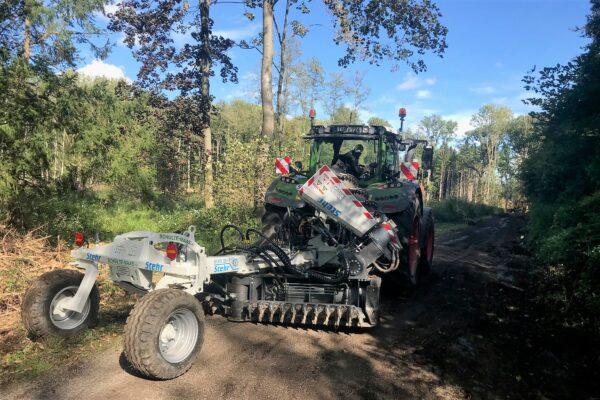 Ein Traktor mit Arbeitsgerät auf einem Waldweg